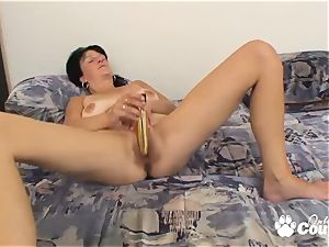 black-haired mummy jerking with large vibrator on couch